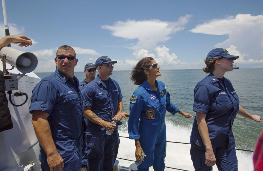 In this Thursday, July 13, 2017 photo, NASA astronaut Suni Williams, second from right, looks out over the Gulf of Mexico where testing of the Orion capsule is taking place about four miles off of Galveston Island, Texas. The testing is the first time since the Apollo program that NASA has practiced such egress techniques from a capsule in open water. (Mark Mulligan/Houston Chronicle via AP)