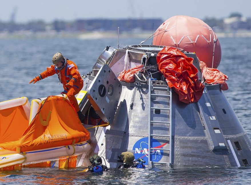 In this Thursday, July 13, 2017 photo, NASA astronaut Mike Fincke jumps into a life raft from an Orion capsule the astronauts are using for a recovery test about four miles off of Galveston Island, Texas in the Gulf of Mexico. The testing is the first time since the Apollo program that NASA has practiced such egress techniques from a capsule in open water. (Mark Mulligan/Houston Chronicle via AP)