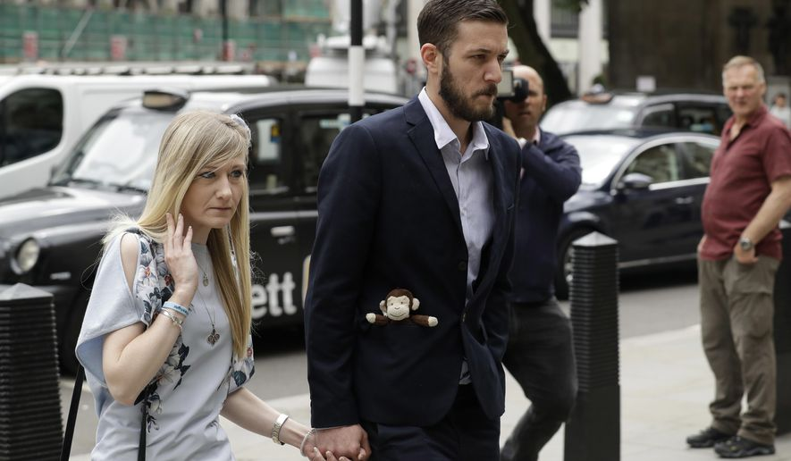 The parents of critically ill baby Charlie Gard, Connie Yates and Chris Gard, right, arrive at the High Court in London, Friday, July 14, 2017. The parents of the 11-month old, who has a rare genetic condition and brain damage, returned to court Friday hoping for a fresh analysis of their wish to take baby Charlie to the United States for medical treatment. (AP Photo/Matt Dunham)