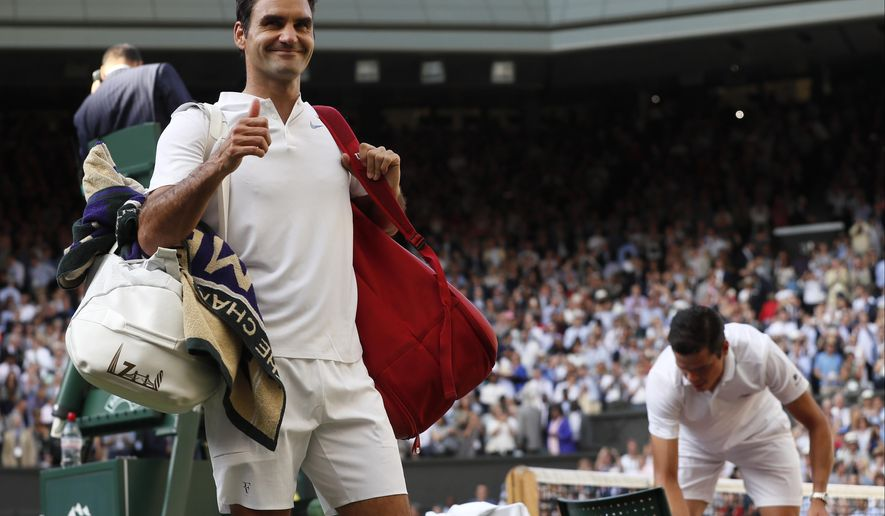Switzerland's Roger Federer, left, celebrates as he leaves the court after beating Canada's Milos Raonic, right, at the end of their Men's Singles Quarterfinal Match on day nine at the Wimbledon Tennis Championships in London Wednesday, July 12, 2017. (AP Photo/Kirsty Wigglesworth)