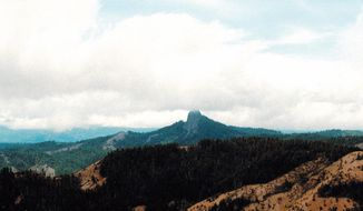 FILE- In this July 6, 2000, file photo, Pilot Rock rises into the clouds in the Cascade-Siskiyou National Monument near Lincoln, Ore. U.S. Secretary of Interior Ryan Zinke will be visiting the Cascade-Siskiyou National Monument in Oregon this weekend as part of the review ordered by President Donald Trump of 27 national monuments established by three former presidents. (AP Photo/Jeff Barnard, File)