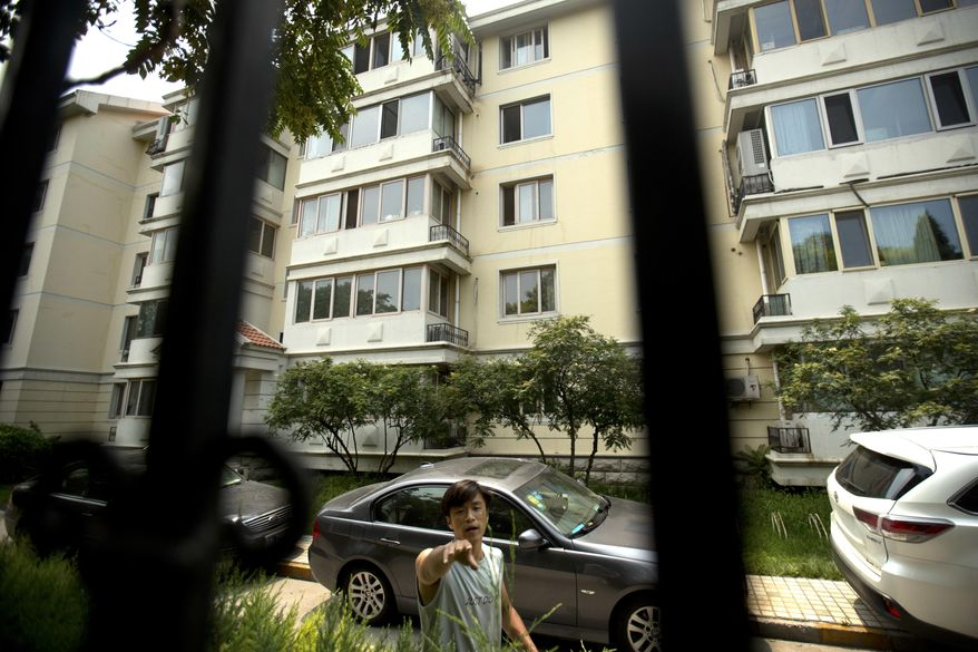 A plainclothes Chinese security guard attempts to stop a photographer from taking photos of an apartment building where Liu Xia, the wife of Chinese dissident and Nobel Prize winner Liu Xiaobo, has been living under house arrest in Beijing, Friday, July 14, 2017. Friends of Liu Xiaobo's family say that efforts to persuade Beijing to allow the couple to leave China were motivated not so much to seek treatment for the terminally ill political prisoner but to facilitate an escape from China for his severely depressed wife, Liu Xia. Liu's death on Thursday, July 13 has now returned his wife's fate back to the fore, with foreign officials calling for Beijing to release her from house arrest and let her leave the country as she wishes. (AP Photo/Mark Schiefelbein)