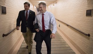 Rep. Ron DeSantis, R-Fla., left, and Rep. Jim Jordan, R-Ohio walk to a meeting with fellow Republicans on Capitol Hill in Washington, Friday, July 14, 2017, to reconcile the GOP's long-overdue budget blueprint, even as divisions between moderates and conservatives over cutting programs like food stamps threaten passage of the measure. The House Budget Committee is expected to vote next week on the plan, which would spend far more money next year than President Donald Trump's proposal. (AP Photo/J. Scott Applewhite)