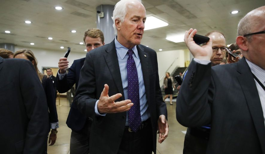 Senate Majority Whip John Cornyn of Texas, center, is pursued by reporters on Capitol Hill in Washington, Tuesday, July 11, 2017. (AP Photo/Jacquelyn Martin)