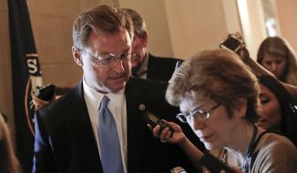 Sen. Dean Heller, R-Nev. speaks to members of the media while walking in the hallways on Capitol Hill in Washington Thursday, July 13, 2017. Senate Majority Leader Mitch McConnell of Ky. plans to roll out the GOP's revised health care bill, pushing toward a showdown vote next week with opposition within the Republican ranks. (AP Photo/Pablo Martinez Monsivais)