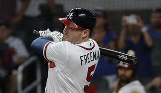 Atlanta Braves' Freddie Freeman (5) follows through on a two-run base hit in the eighth inning of a baseball game against the Arizona Diamondbacks, Friday, July 14, 2017, in Atlanta. (AP Photo/John Bazemore)