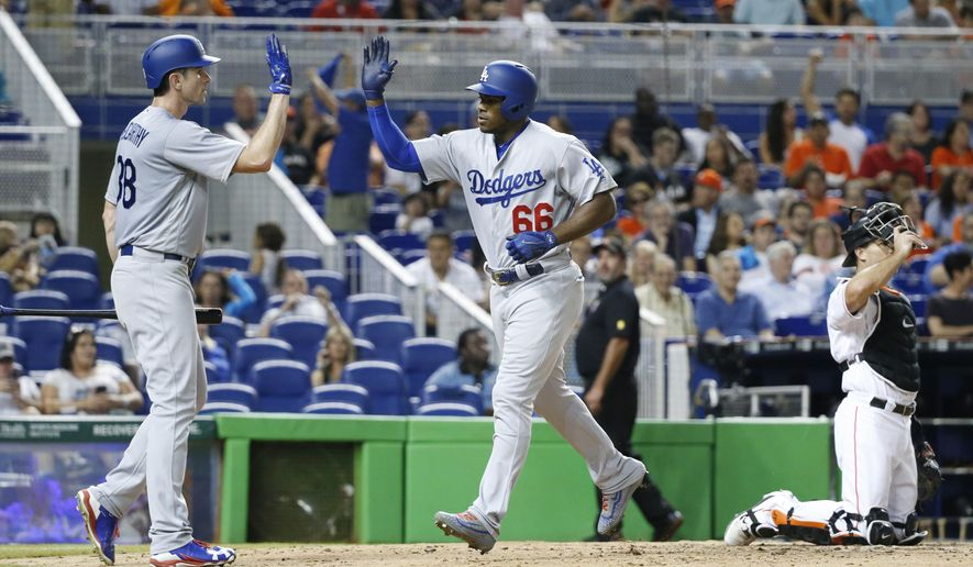 Los Angeles Dodgers' Yasiel Puig (66) is congratulated by Brandon McCarthy after Puig hit a home run during the fifth inning of the team's baseball game against the Miami Marlins, Friday, July 14, 2017, in Miami. (AP Photo/Wilfredo Lee)