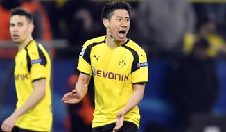 FILE - In this Wednesday, April 12, 2017 file photo, Dortmund's Shinji Kagawa celebrates after scoring his side's second goal during the Champions League quarterfinal first leg soccer match between Borussia Dortmund and AS Monaco in Dortmund, Germany. Japan star Shinji Kagawa has extended his contract with Borussia Dortmund contract by two years until June 2020. (AP Photo/Martin Meissner, File)