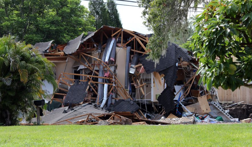 Debris is strewn about from a partially collapsed home in Land O' Lakes, Fla. on Friday, July 14, 2017.A sinkhole that started out the size of a small swimming pool and continued to grow has swallowed a home in Florida and severely damaged another. (Alessandra da Pra/Tampa Bay Times via AP)