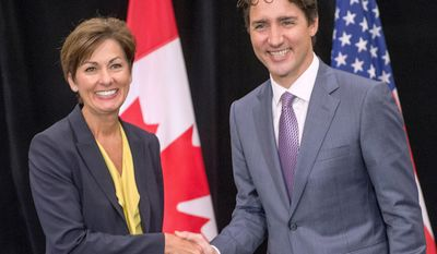 """Prime Minister Justin Trudeau, right, meets with Iowa Governor Kim Reynolds during a special session called """"Collaborating to Create Tomorrow's Global Economy"""" at the second day of the National Governors Association meeting Friday, July 14, 2017, in Providence, R.I. (Ryan Remiorz/The Canadian Press via AP)"""