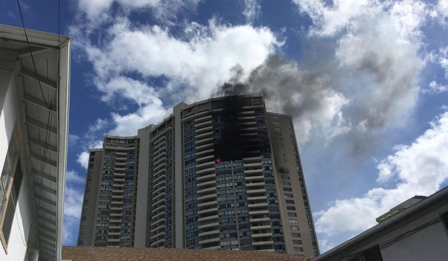 Smoke billows from a high-rise apartment building in Honolulu, Friday, July 14, 2017. Dozens of firefighters are battling the multiple-alarm fire at Marco Polo apartments that Honolulu Fire Department spokesman Capt. David Jenkins said started on the 26th floor and has spread to other units. (AP Photo/Audrey McAvoy)