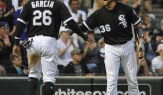 Chicago White Sox's Kevan Smith (36) celebrates with teammate Avisail Garcia (26) after Garcia scored on a Tyler Saladino ground rule double during the second inning of a baseball game against the Seattle Mariners Friday, July 14, 2017, in Chicago. (AP Photo/Paul Beaty)