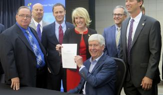 Michigan Gov. Rick Snyder smiles after signing a $56.5 billion state budget on Friday, July 14, 2017, at the Kent Intermediate School District Career Tech Center in Grand Rapids, Mich. Looking on from left are: state Superintendent Brian Whiston; budget director Al Pscholka; House Speaker Tom Leonard; House Appropriations Chairwoman Laura Cox; Rep. Chris Afendoulis; and Senate Appropriations Chairman Dave Hildenbrand. (AP Photo/David Eggert)