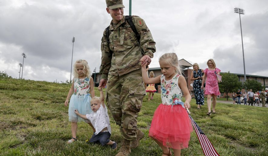 Capt. Steve Preston walks with his children Molly, right, Emily, left, and Tommy, second left, as his wife Amber walks behind right, following a welcoming ceremony in Lincoln, Neb., Thursday, July 13, 2017, for about 90 Nebraska Army National Guard soldiers, members of the 1st Infantry Division Main Command Post-Operational Detachment, who had met their families for the first time after spending the last 9 months deployed in Iraq. (AP Photo/Nati Harnik)
