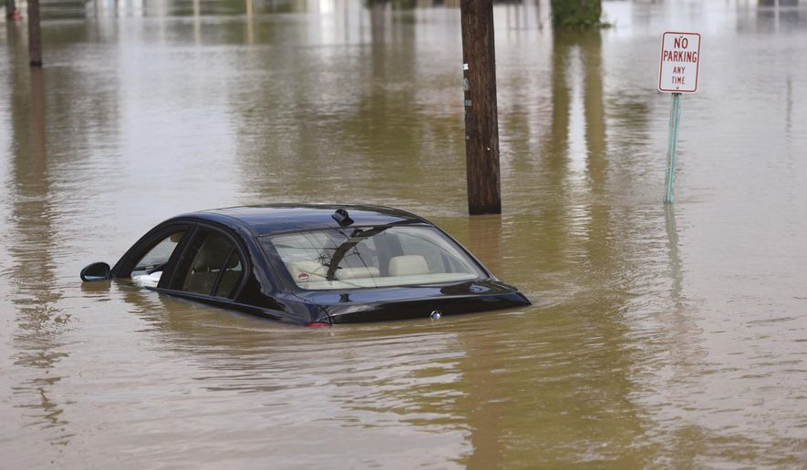 A BMW is stranded in floodwaters on Clinton Ct. in Findlay, Ohio, Friday, July 14, 2017. The Blanchard river was expected to crest Friday afternoon.(Randy Roberts/The Courier via AP)