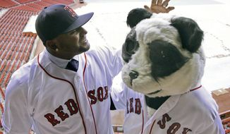 FILE - In this Nov. 25, 2014, file photo, then-Boston Red Sox free agent third baseman Pablo Sandoval, nicknamed Kung Fu Panda, converses with a person dressed as a panda bear wearing a Red Sox jersey, overlooking a tarp-covered Fenway Park field in Boston. On Friday, July 14, 2017, the Red Sox announced that Sandoval had been designated for assignment after being activated from the 10-day disabled list. (AP Photo/Stephan Savoia, File)