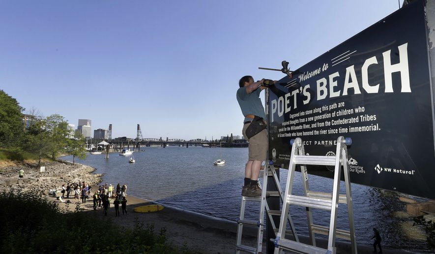 In this Thursday, July 6, 2017 photo, Curt Ellsworth puts up a sign at a section of newly formed beach, named Poet's Beach, on the Willamette River in downtown Portland, Ore. Portland is well-known as a tree-hugging, outdoorsy city, but the river that powers through its downtown has never been part of that green reputation. For decades, residents have been repulsed by the idea of swimming in the Willamette River because of weekly sewage overflows that created a bacterial stew. Now, the recent completion of a $1.4 billion sewage pipe has flushed those worries - and the river once shunned by swimmers is enjoying a rapid renaissance.  (AP Photo/Don Ryan)