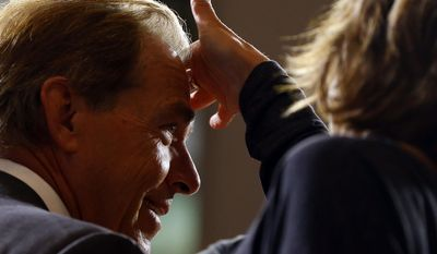 A woman fixes Alabama NCAA college football coach Nick Saban's hair before going on air during the Southeastern Conference's annual media gathering, Wednesday, July 12, 2017, in Hoover, Ala. (AP Photo/Butch Dill)
