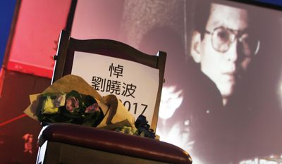 A bouquet of flowers is placed on a chair that reads: ''Mourning Liu Xiaobo'' in front of his image during a ceremony to mourn late Nobel Peace Prize laureate Liu, China's most famous political prisoner, at Democracy Square in Taipei, Taiwan, Friday, July 14, 2017. Liu died Thursday of liver cancer at 61. (AP Photo/Chiang Ying-ying)