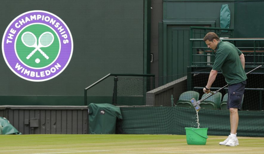 Ben Sidgwick, wrings out his mop, on Center Court at the All England Club on day nine at the Wimbledon Tennis Championships in London Thursday, July 13, 2017. A team of 32 people spreads out around the All England Club grounds to mow, paint and mop _ yes, with a sponge mop and a pail of water, the same sort of equipment folks might use to clean a kitchen floor, except this is done with a delicate touch. (AP Photo/Alastair Grant)