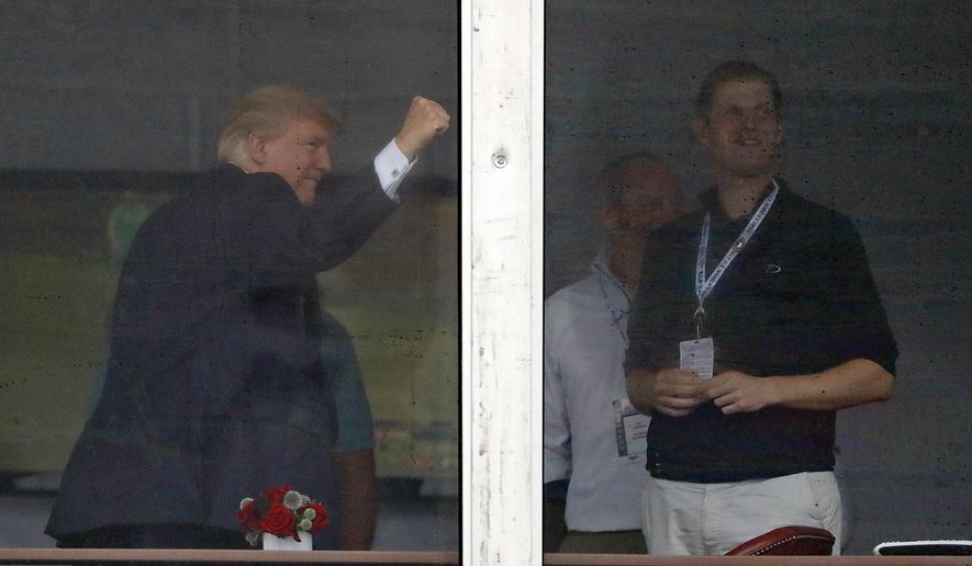 President Donald Trump pumps his fist as he reacts to spectators from a viewing platform with his son Eric Trump, right, near the 15th green during the second round of the U.S. Women's Open Golf tournament Friday, July 14, 2017, in Bedminster, N.J. (AP Photo/Julie Jacobson)