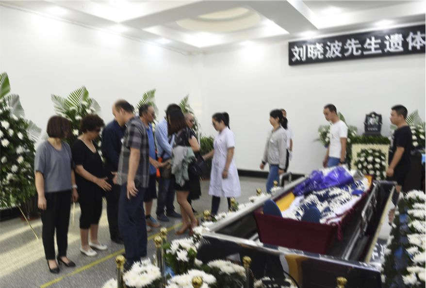 ADDS A DROPPED WORD IN FIRST SENTENCE - In this photo provided by the Shenyang Municipal Information Office, people attend the funeral of jailed Nobel Peace Prize winner and Chinese dissident Liu Xiaobo at a funeral parlor in Shenyang in northeastern China's Liaoning Province, Saturday, July 15, 2017. China cremated the body of imprisoned Nobel Peace Prize laureate Liu Xiaobo, who died this week after a battle with liver cancer amid international criticism of Beijing for not letting him travel abroad as he had wished. (Shenyang Municipal Information Office via AP)