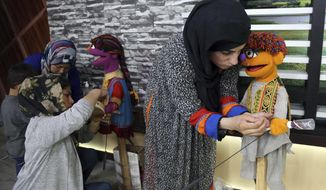 In this Monday, July 10, 2017 photo, Afghan puppeteers setting props for Sesame Street's new Afghan character, a 4-year-old Afghan puppet boy called Zeerak, right, and Zari, before a recoding a segment for Afghan version of Sesame Street called Baghch-e-Simsim for the sixth season of the program aired on TOLO a Local Television station in Kabul, Afghanistan. (AP Photo/Rahmat Gul)
