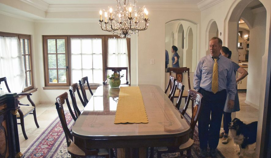 """ADVANCE FOR WEEKEND USE JULY 15, 2017 AND THEREAFTER - In this Thursday, July 6, 2017 photo, Mark Choate, right, walks in the mansion's dining room in their renovated home in Juneau, Alaska. Choate expects his new house to last for 1,000 years. """"My idea was to build a house that will last 1,000 years,"""" After eight years and several million dollars, he may have just that. The secret passageway, elevator, wine cellar, and tower-top study are added bonuses. (James Brooks/The Juneau Empire via AP)"""