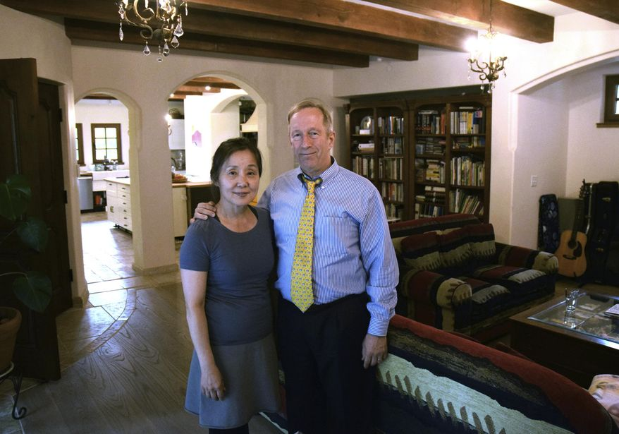 ADVANCE FOR WEEKEND USE JULY 15, 2017 AND THEREAFTER - In this Thursday, July 6, 2017 photo, Sun Hee and Mark Choate stand in the living room of their new home in Juneau, Alaska. Mark and Sun Hee Choate bought their home in 1991, paying about $270,000. At that time, the home was more than 75 years old. Its purple and green shag carpeting and tacky wallpaper were saturated with nicotine from a previous owner, and the asking price was $40,000 more than the assessed value. (James Brooks/The Juneau Empire via AP)