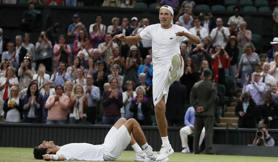 Poland's Lukasz Kubot, right, and Brazil's Marcelo Melo who lies on the floor celebrate after defeating Austria's Oliver Marach, and Croatia's Mate Pavic in the Men's Doubles final match on day twelve at the Wimbledon Tennis Championships in London, Saturday, July 15, 2017. (AP Photo/Kirsty Wigglesworth)