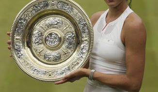 Spain's Garbine Muguruzam hold the trophy after defeating Venus Williams of the United States in the Women's Singles final match on day twelve at the Wimbledon Tennis Championships in London Saturday, July 15, 2017. (AP Photo/Tim Ireland)