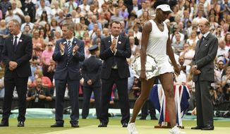 Venus Williams of the United States holds the runners-up plate after losing to Spain's Garbine Muguruza in the Women's Singles final match on day twelve at the Wimbledon Tennis Championships in London Saturday, July 15, 2017. (David Ramos/Pool Photo via AP)