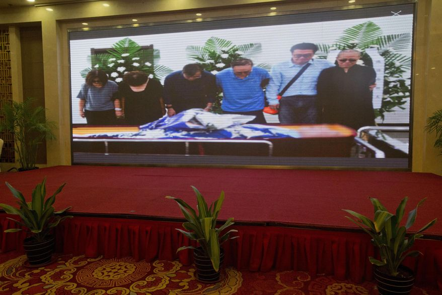 A photo showing from right Liu Xia, her brother Liu Hui, Liu Xiaobo's elder brother Liu Xiaoguang and younger brother Liu Xiaoxuan attend a ceremony for the late Nobel Peace Prize Laureate Liu Xiaobo at a funeral home is shown at a government press conference held at a hotel in Shenyang in northeastern China's Liaoning Province, Saturday, July 15, 2017. China cremated the body of imprisoned Nobel Peace Prize laureate Liu Xiaobo, who died this week after a battle with liver cancer amid international criticism of Beijing for not letting him travel abroad as he had wished. (AP Photo/Ng Han Guan)