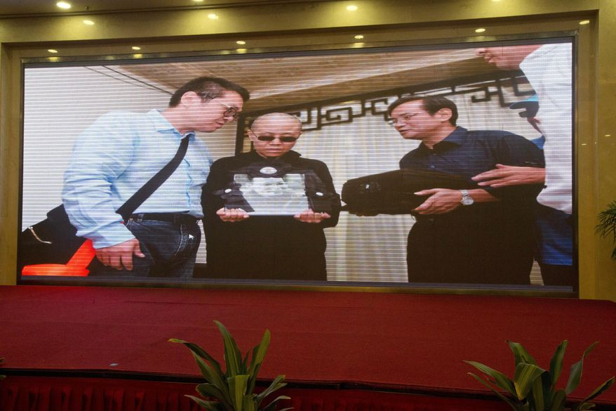 A photo showing Liu Xia, center, holding a photo of the late Liu Xiaobo as Liu Xiaoxuan, Liu Xiaobo's younger brother, right, holds his cremated remains in a black box near Liu Xia's brother Liu Hui, left, during a ceremony, is displayed at a government press conference held in a hotel in Shenyang in northeastern China's Liaoning Province, Saturday, July 15, 2017. China cremated the body of imprisoned Nobel Peace Prize laureate Liu Xiaobo, who died this week after a battle with liver cancer amid international criticism of Beijing for not letting him travel abroad as he had wished. (AP Photo/Ng Han Guan)