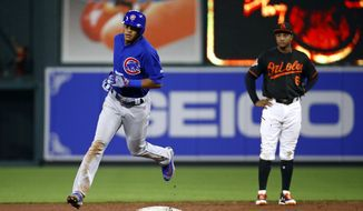 Chicago Cubs' Addison Russell, left, rounds the bases past Baltimore Orioles second baseman Jonathan Schoop after hitting a solo home run in the ninth inning of a baseball game in Baltimore, Friday, July 14, 2017. Chicago won 9-8. (AP Photo/Patrick Semansky)