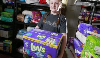 In this June 27, 2017, photo, Kayla Smith, 11, poses for a photo at the Jerome United Methodist Church in Plain City, Ohio. Smith collects thousands of diapers each year as part of the Diaper Angels program at the church. (Barbara J. Perenic/The Columbus Dispatch via AP)