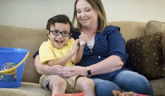 ADVANCE FOR SATURDAY, JULY 15 - In this June 27, 2017 photo, Kate Plock holds her son Mason Plock-Sisiutho during an interview Tuesday, June 27, 2017, in Omaha, Neb. When Kate Plock first came from Pawnee City to the Ronald McDonald House in Omaha, she thought she'd be staying about two months _ long enough for her then-3-year-old son Mason to undergo feeding therapy. What was supposed to be an eight-week stay has stretched to nearly two years, well past the Ronald McDonald House limit of 15 months. (Kent Sievers/The World-Herald via AP)/Omaha World-Herald via AP)