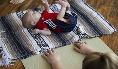 ADVANCE FOR USE SATURDAY, JULY 15 - In this Friday, June 30, 2017 photo, three-month-old Jensen Gonne joins his mom, Katie, during the postpartum yoga class at Vancouver Wellness Studio in Vancouver, Wash. (Amanda Cowan/The Columbian via AP)