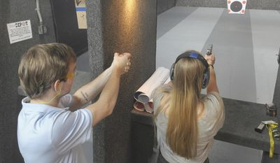 In this June 2017 photo, William Daugherty instructs Darrah Dunagan, 18, how to safely fire a handgun in Shooter's Depot indoor firing range, in Chattanooga, Tenn. (Alex McMahan/Tennessee Ledger via AP)