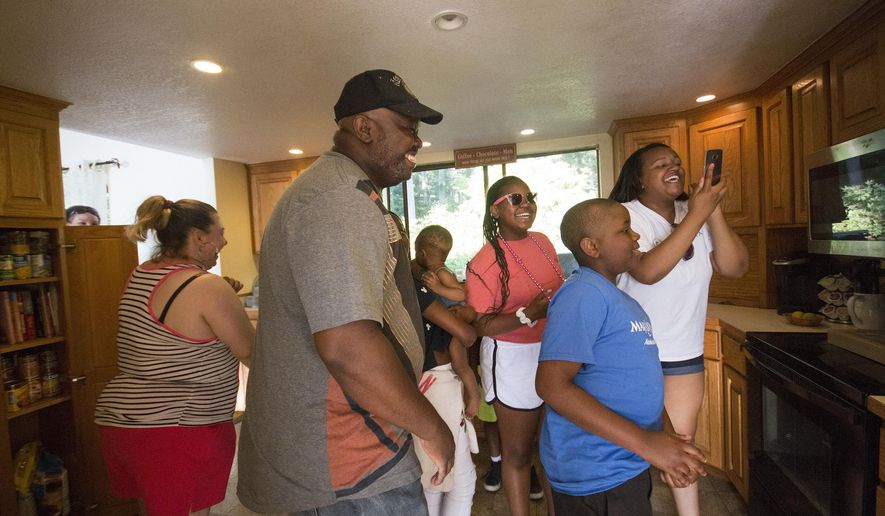 ADVANCE FOR USE SATURDAY, JULY 15 - In this Thursday, July 6, 2017 photo, the Randle family looks around their kitchen to see that there are no more broken cabinets after friends and family renovated their home in Poulsbo, Wash. (Michaela Roman/Kitsap Sun via AP)