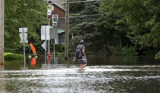 """A man walks on a flooded street Friday, July 14, 2017, in Gurnee, Ill. Illinois officials said Friday that several thousand buildings have been affected by """"unprecedented"""" flooding north of Chicago, and the damage is expected to worsen this weekend as water flows down rivers into the state from Wisconsin. (AP Photo/G-Jun Yam)"""