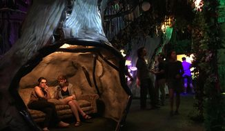 Recent high school graduates Abbigail Deason and Grace Branscum, both 18, of Oklahoma City relax inside Meow Wolf's mazelike exhibition space in Santa Fe, N.M., on Friday, July 14, 2017. The startup company behind the popular art installation is seeking out small-scale Internet investors as it lays the groundwork for expansion to major metropolitan markets.