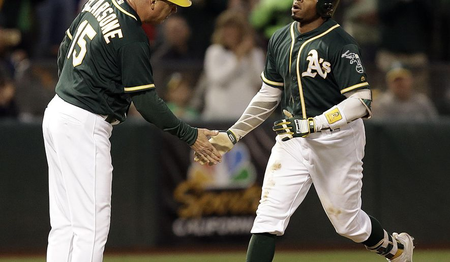 Oakland Athletics' Khris Davis, right, is congratulated by third base coach Steve Scarsone after hitting a home run off Cleveland Indians' Carlos Carrasco during the fifth inning of a baseball game Friday, July 14, 2017, in Oakland, Calif. (AP Photo/Ben Margot)