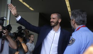Italy defender Leonardo Bonucci waves to fans as he walks off AC Milan's headquarters, in Milan, Italy, Friday, July 14, 2017. Bonucci is close to completing a transfer from Juventus to rival AC Milan that could signal a shift in the balance of power in Serie A. (AP Photo/Luca Bruno)