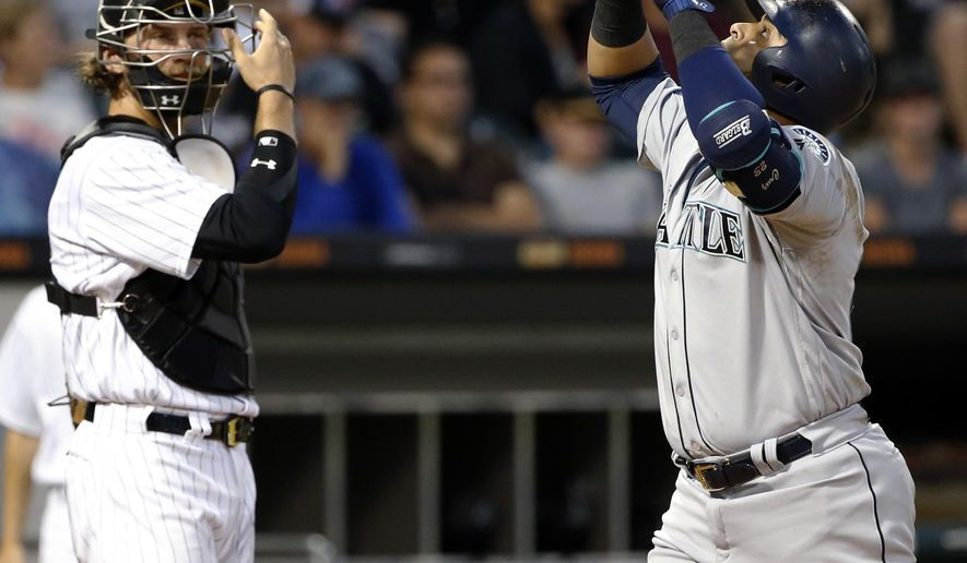 Seattle Mariners' Nelson Cruz, right, celebrates after hitting a two-run home run as Chicago White Sox catcher Kevan Smith looks to the field during the sixth inning of a baseball game Saturday, July 15, 2017, in Chicago. (AP Photo/Nam Y. Huh)