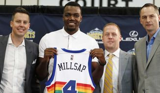 In this July 13, 2017, file photo, Denver Nuggets new NBA basketball forward Paul Millsap, second from left, holds up his new jersey as Josh Kroenke, team president and governor, left, Tim Connelly, president of basketball operations and Arturas Karnisovas, general manager of the Nuggets, join in for a photograph during Millsap's introduction to the media at a news conference in Denver. The NBA has for years had an issue with the Western Conference being superior to the East, but next season promises to have the widest talent gap yet after a flurry of stars left their teams in the East to try to challenge the mighty Warriors in the West. (AP Photo/David Zalubowski, File) **FILE**