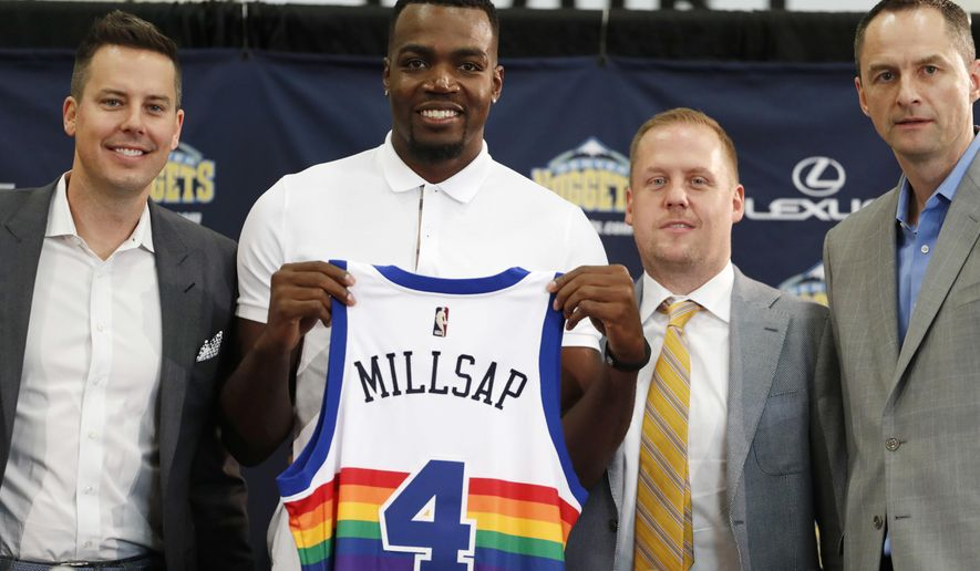 FILE - In this July 13, 2017, file photo, Denver Nuggets new NBA basketball forward Paul Millsap, second from left, holds up his new jersey as Josh Kroenke, team president and governor, left, Tim Connelly, president of basketball operations and Arturas Karnisovas, general manager of the Nuggets, join in for a photograph during Millsap's introduction to the media at a news conference in Denver. The NBA has for years had an issue with the Western Conference being superior to the East, but next season promises to have the widest talent gap yet after a flurry of stars left their teams in the East to try to challenge the mighty Warriors in the West. (AP Photo/David Zalubowski, File)