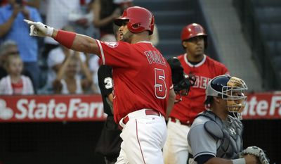 Los Angeles Angels' Albert Pujols points to the crowd as he walks past Tampa Bay Rays catcher Wilson Ramos after hitting a home run during the second inning of a baseball game, Friday, July 14, 2017, in Anaheim, Calif. (AP Photo/Jae C. Hong)