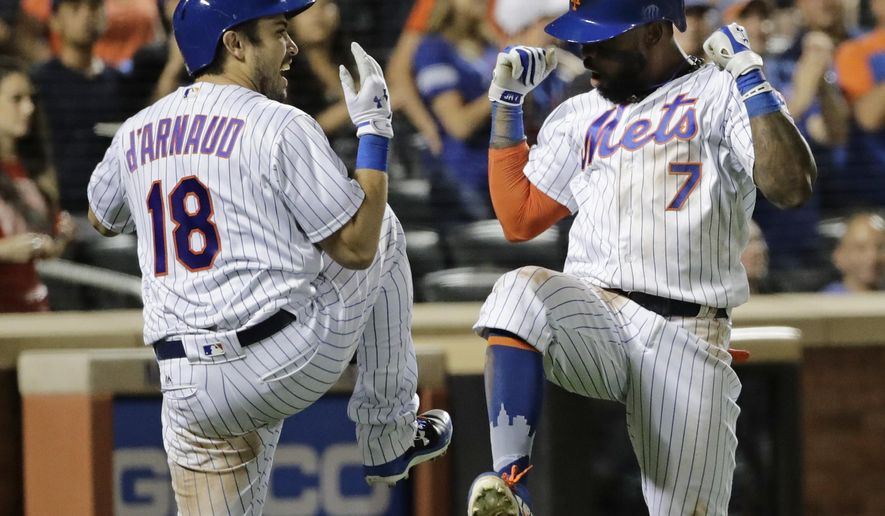 New York Mets' Travis d'Arnaud (18) celebrates with Jose Reyes (7) after Reyes hit a home run during the eighth inning of a baseball game against the Colorado Rockies on Saturday, July 15, 2017, in New York. (AP Photo/Frank Franklin II)