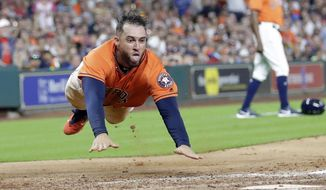 Houston Astros' George Springer dives toward home plate to score on a single by Josh Reddick during the third inning of the team's baseball game against the Minnesota Twins Friday, July 14, 2017, in Houston. (AP Photo/David J. Phillip)